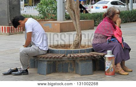 Man And Woman Are Sitting On The Bench In Park, Kunming