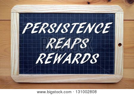 The words Persistence Reaps Rewards in white text on a blackboard as a reminder it pays to make an effort