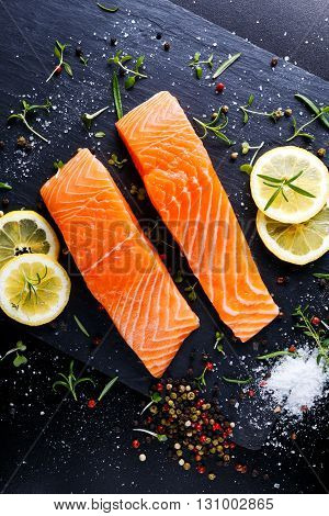 fresh raw salmon fillet with aromatic herbs, spices on stone background.