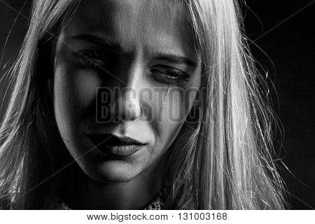 sad woman crying on black background monochrome