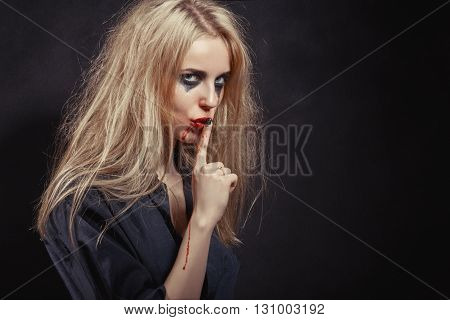 Young Woman With Red Hairs Gesturing For Being Quiet Shows Silence Sign In Dark Background With Copyspace