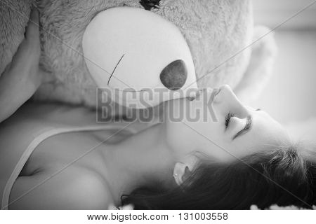 sensual girl lying with teddy bear monochrome image