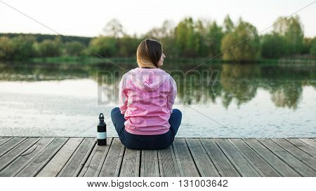 Young city resident enjoy the tranquility on a pier near the pond