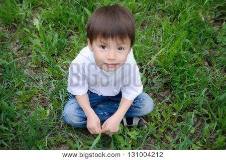 Boy Sitting On The Grass Outside