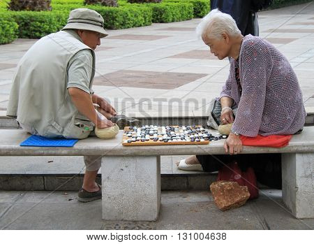 Man And Woman Are Playing Go In The Park Of Kunming, China