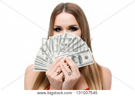 Closeup portrait on white background of woman with beautiful eyes and a lot of money. The girl covers her face to eye dollars. Bright makeup, smoky, light hair, perfect eyebrows