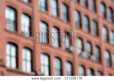 Defocused windows of an old New York City brick building.