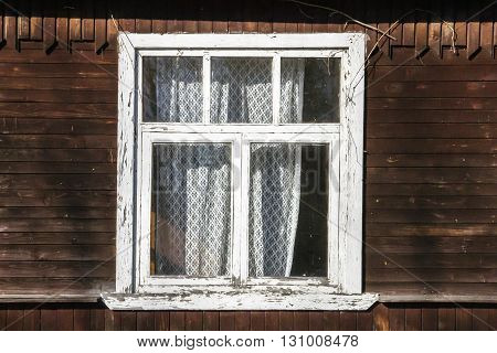 old wooden window with frame painted white peeling paint on wooden plank wall of village house