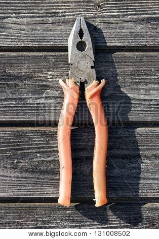shabby combination pliers with red plastic handles hanging on wooden board wall closeup