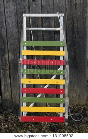 color wood and metal children sledges at the wooden board wall