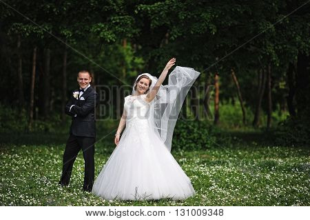 Elegance Wedding Couple On Field Of Flowers Background Wood, Bride Throws A Veil