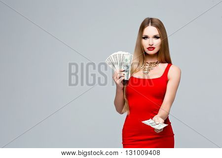 Portrait of glamorous young woman in red dress with bright makeup, red lips, a gold necklace. The woman holds in hands a lot of money, with the other hand gives money to you