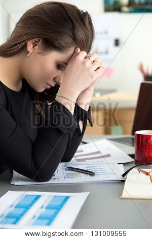 Tired female employee at workplace in office touching her head. Sleepy worker early in the morning after late night work. Overworking making mistake stress termination or depression concept