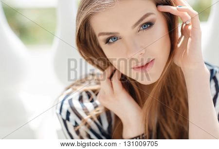 Portrait of a happy woman in spring city,blonde long straight hair,blue eyes,beautiful white teeth and nice smile,light makeup,wearing a thin striped blouse with white and black stripes,spends time in the city enjoying the Sunny day