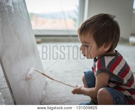 Little cute boy painting on a wall