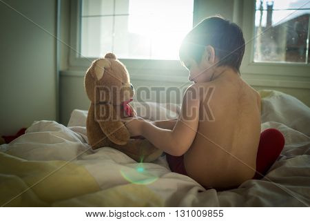 A little cute child with Teddy bear on the bed