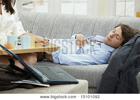 Young businessman resting on couch, woman holding breakfast tray.