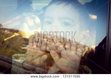 Little boy looking through window