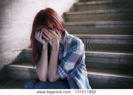 Girl in adolescent crisis sitting on the steps of a basement covers her face with her hands. A natural light penetrates from above.