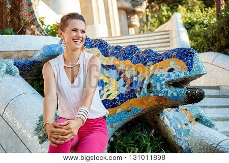 Smiling Woman Sitting Near Mosaic Dragon In Park Guell, Spain
