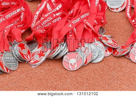 STOCKHOLM SWEDEN - MAY 14 2016: Lots of medals laying on the race track from the Tough Viking Event in Sweden April 14 2016