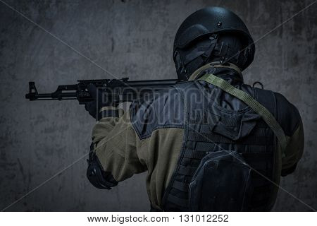 Terrorist Soldier In A Camouflage And Helmet With Rifle Near The Concrete Wall