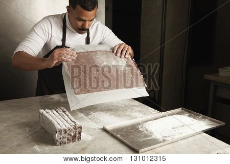 Black Man Chief Preparing Freshly Baked Chocolate Cake For Packaging, Artisan Cooking Process In Con