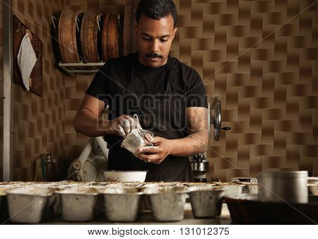 Black Man Chief Is Preparing Cake Molds Before Fill Them With Batter In His Professional Artisan Con