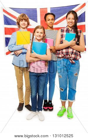 Full-length picture of multi ethnic teenage students standing with textbooks against British flag, isolated on white