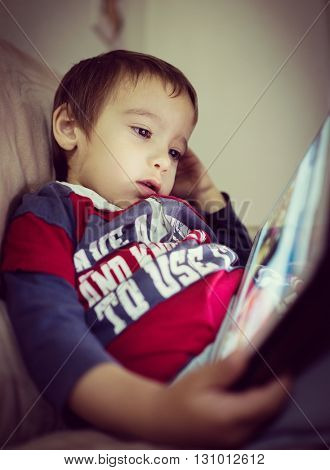 Little boy with tablet on sofa