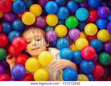Baby boy playing in pool with colorful balls