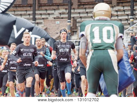 STOCKHOLM SWEDEN - MAY 14 2016: Lots of runners trying to pass the first obstracle american football players after the start in the obstacle race Tough Viking Event in Sweden April 14 2016
