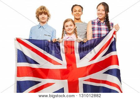 Four multiethnic teenage kids standing behind British flag, isolated on white background