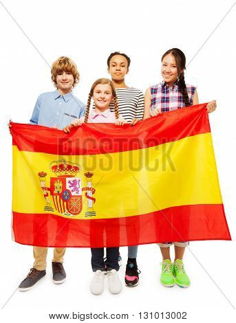 Group of four happy multiethnic teenage kids standing behind the flag of Spain, isolated on white