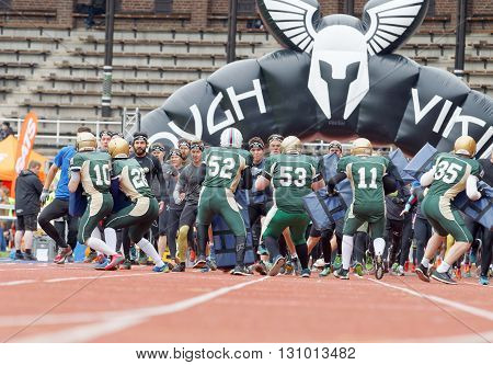 STOCKHOLM SWEDEN - MAY 14 2016: Lots of runner fighting to pass the first obstacle american football players after the start in the obstacle race Tough Viking Event in Sweden April 14 2016