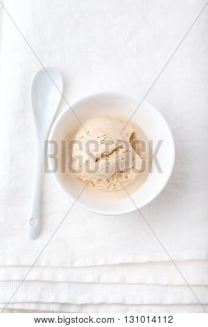 Ice cream with Earl grey tea flavor in white ceramic bowl on a white textile background Homemade Organic product Top view
