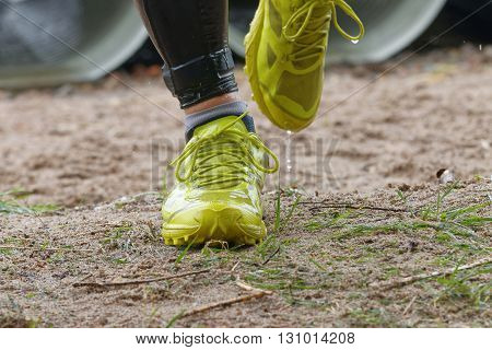 STOCKHOLM SWEDEN - MAY 14 2016: Closeup of yellow wet shoes running in the obstacle race Tough Viking Event in Sweden April 14 2016
