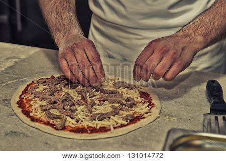 Making of a meat pizza in a restaurant, toned image