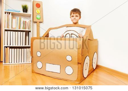 Creative kid boy plays with his handmade cardboard car at home