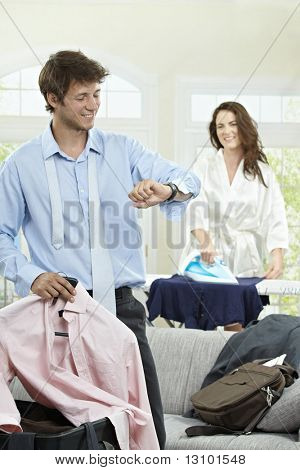 Young businessman going to business trip, looking at his watch. Woman ironing in the background.