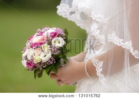 Colored bouquet in bride's hands with blurred background