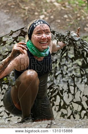 STOCKHOLM SWEDEN - MAY 14 2016: Smiling woman covered with mud crawling under a camouflage net in the obstacle race Tough Viking Event in Sweden April 14 2016