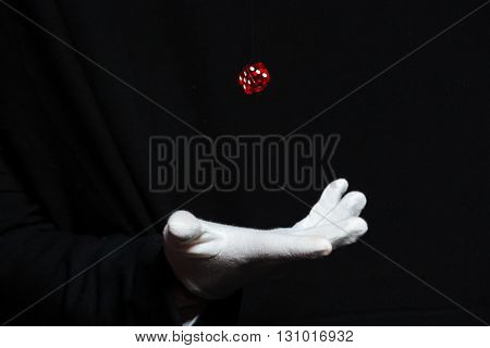 Hand of man magician in white glove showing tricks with dice flying in the air over black background