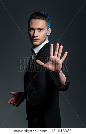 Handsome young man magician showing his palm over grey background