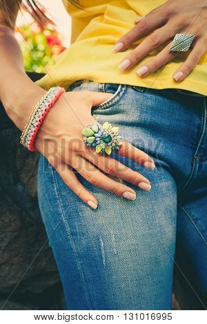 woman hand on blue jeans with big colorful ring and bracelet summer trendy bijou
