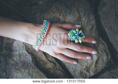 closeup of female hand with colorful  ring and bracelet on stone