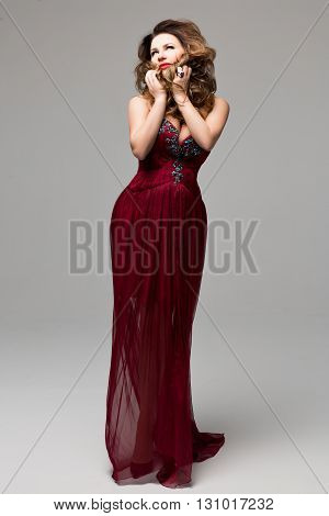 Beautiful young female I in a long red dress with precious stones on a gray background. Clothing catalog, catalog design. Chic design of the dress. Evening makeup, red lips, wavy hair
