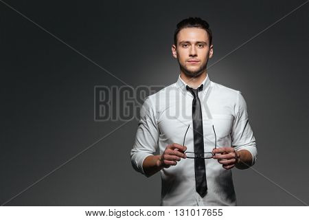 Attractive young businessman in white shirt and tie holding glasses over grey background