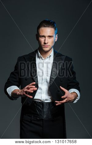 Concentrated young man magician in black tail coat conjuring tricks over grey background