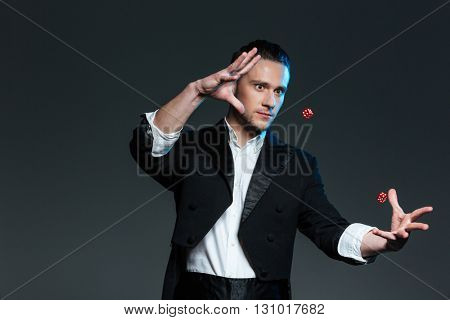 Handsome young man magician showing tricks with flying dice over grey background